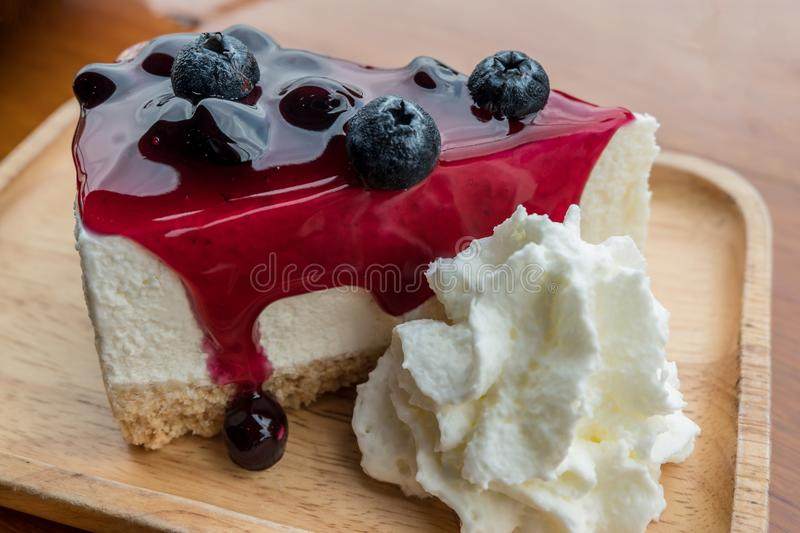 Blueberry cheese cake with whipping cream. Close up of blueberry cheese cake with whipping cream on wooden plate stock image