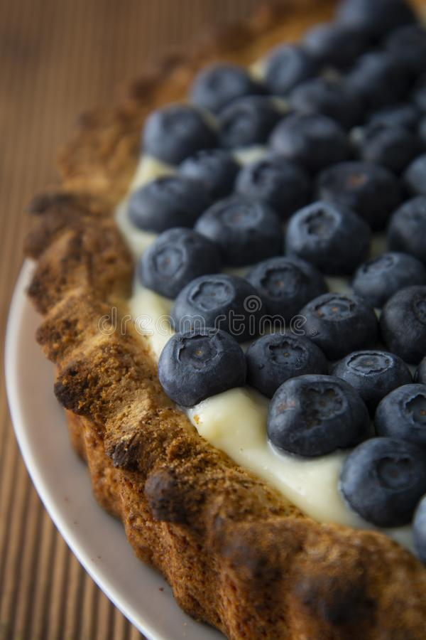 Close up blueberry tart or cake with cream and berries. Fresh sweet dessert with fruits. Homemade food, wooden, rustic background royalty free stock images