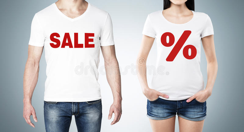 Close up of the bodies of man and woman in a white t-shirts with the red percentage sign and the word ' sale ' on the chest. royalty free stock image
