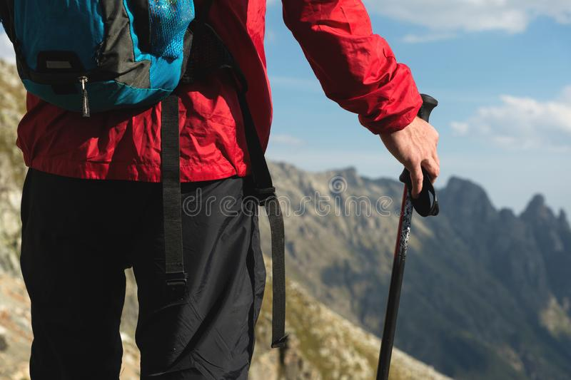 Close up body of man with a backpack and trekking poles stands on top of a rock against the background rocky valley high. In the mountains. The concept of royalty free stock image