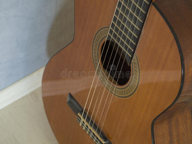 Close up body of spanish acoustic guitar focused on strings royalty free stock image