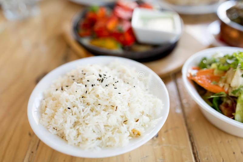 Close up of boiled rice in bowl on table. Food, south asian cuisine, culinary and cooking concept - close up of boiled rice in bowl on table of indian restaurant stock image