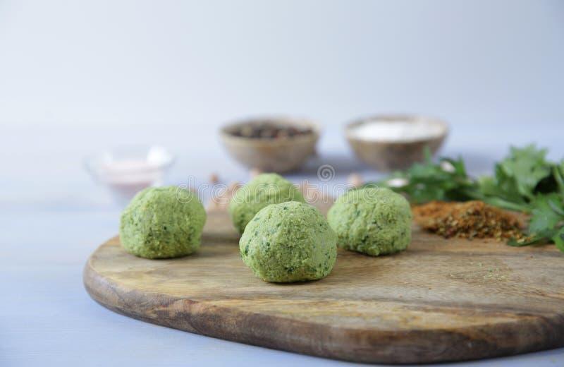 Close-up Bolas cruas frescas do falafel dos grãos-de-bico, das ervas e das especiarias em uma placa de corte de madeira em um fun imagens de stock