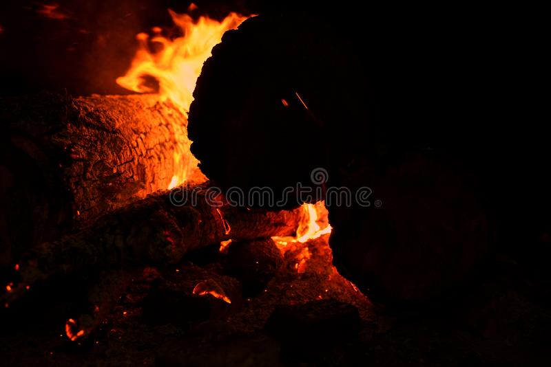 Close up of bonfire with a sparks at night. Heat from burning logs and coals in the dark royalty free stock photo