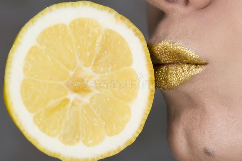 Close up bonito com os bordos f?meas com composi??o da cor do ouro e fatia do lim?o beijo Cosm?ticos do brilho imagens de stock royalty free