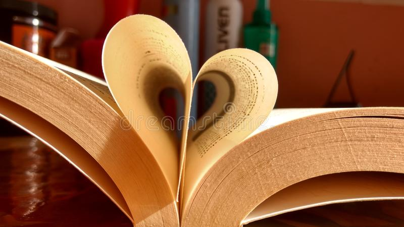 Close-up of the book opened, which the book sheet rolled into a heart shape selective focus and shallow depth of field.  stock photo