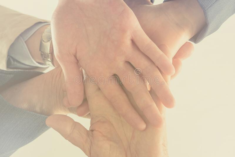 Close up bottom view business people putting their hands together. Arms consolidation, Teamwork concept. royalty free stock image