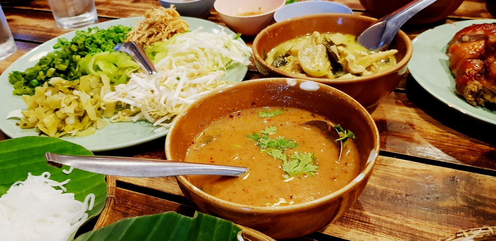 Close up bowl of spicy fish curry sauce on wooden table with Thai rice noodle, vegetable, grilled chicken and green curry stock photo