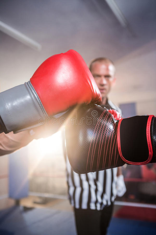 Close-up of boxers punching fists against referee stock photography