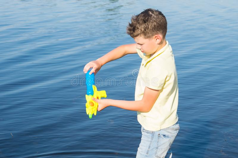 Close-up of a boy drawing water into a pistol against the backdrop of a lake to play stock photos
