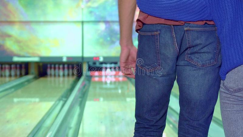 Boy and girl hug each other at the bowling. Close up of boy and girl hugging each other at the bowling. Redhead women knock down few pins. Man coming close to royalty free stock photo