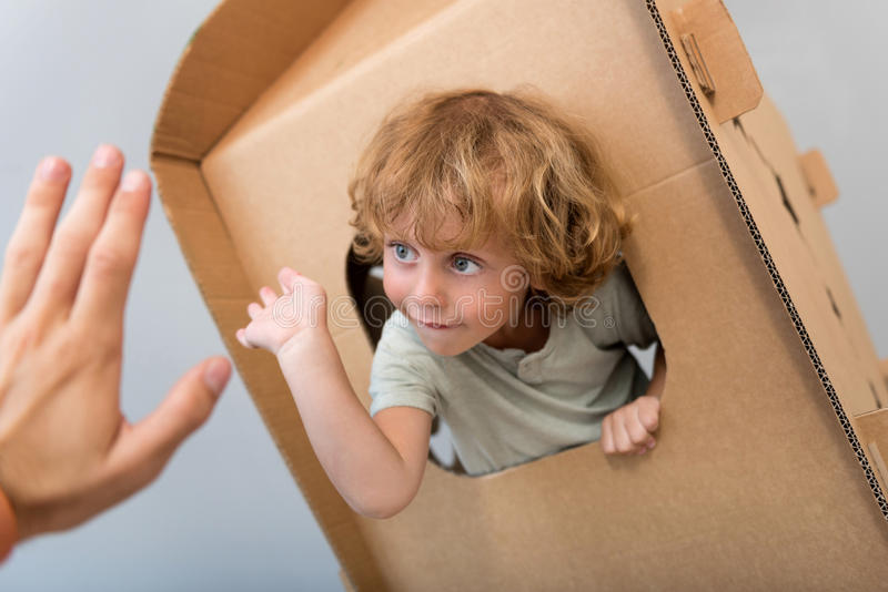 Close up of boy giving five. Take it. Captivating little boy sitting in the carton rocket and giving five to a hand of a man through the window stock photography