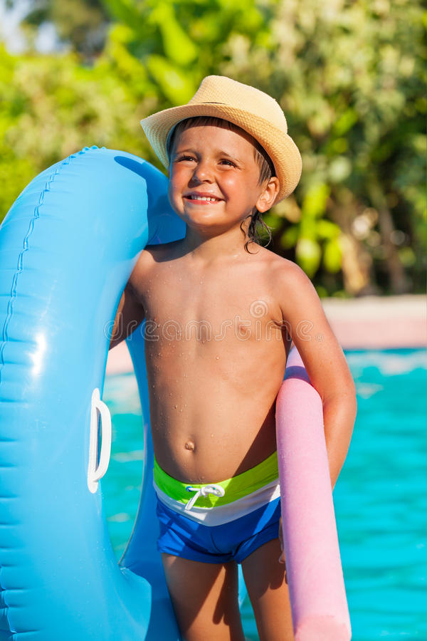 Close-up of boy with inflatable ring, pool noodle. Close-up of boy in hat holding inflatable ring and pool noodle standing near the swimming pool outside in stock images
