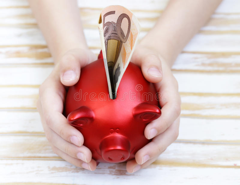 Close up of boy's hands holding piggy bank stock image