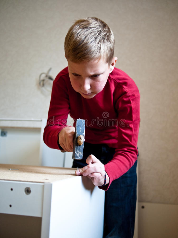 Close-up of a boy standing with a hammer stock images