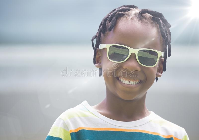 Close up of boy in sunglasses against blurry beach with flare. Digital composite of Close up of boy in sunglasses against blurry beach with flare royalty free stock photos