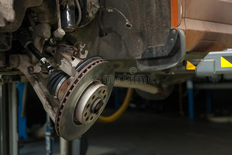 A close-up on  brake system of a car with pads, discs, a caliper on a lift in a vehicle repair workshop. Auto service industry royalty free stock image