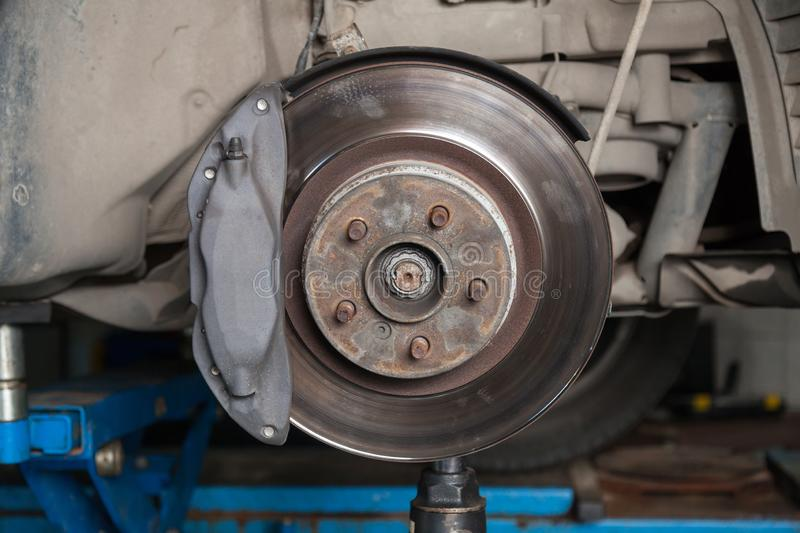 A close-up on  brake system of a car with pads, discs, a caliper on a lift in a vehicle repair workshop. Auto service industry stock photos