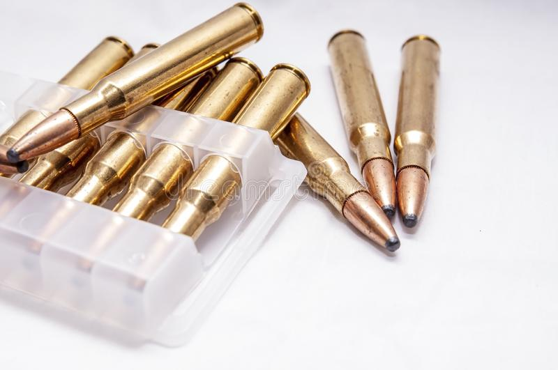 A close up of brass rifle bullets used for hunting, some in a plastic case. On a white background royalty free stock images