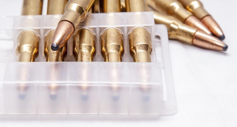 A close up of brass rifle bullets used for hunting, some in a plastic case. On a white background royalty free stock photography