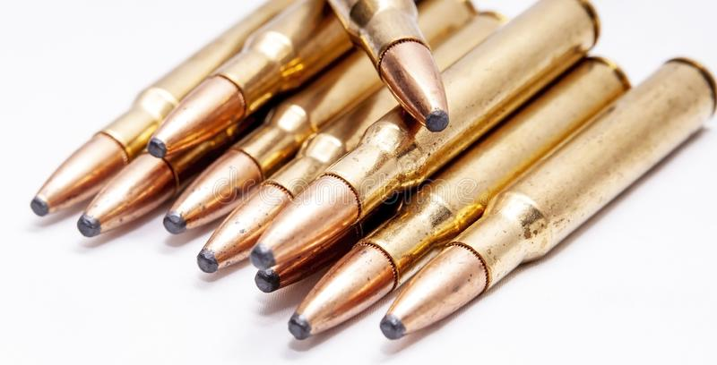 A close up of brass rifle bullets used for hunting. On a white background stock photo