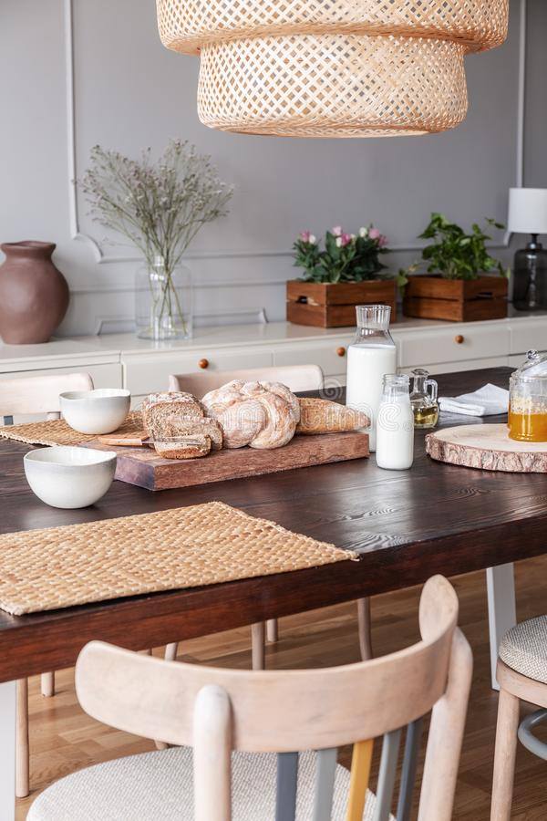 Close-up of bread, milk and food mat on a table in a kitchen interior on a countryside stock photography