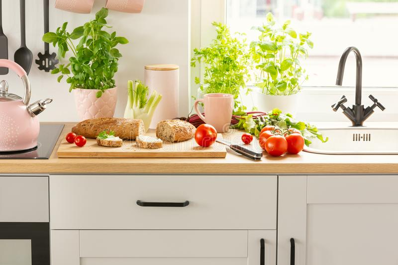 Close-up of bread, tomatoes and plants on a countertop in a kitchen interior royalty free stock image