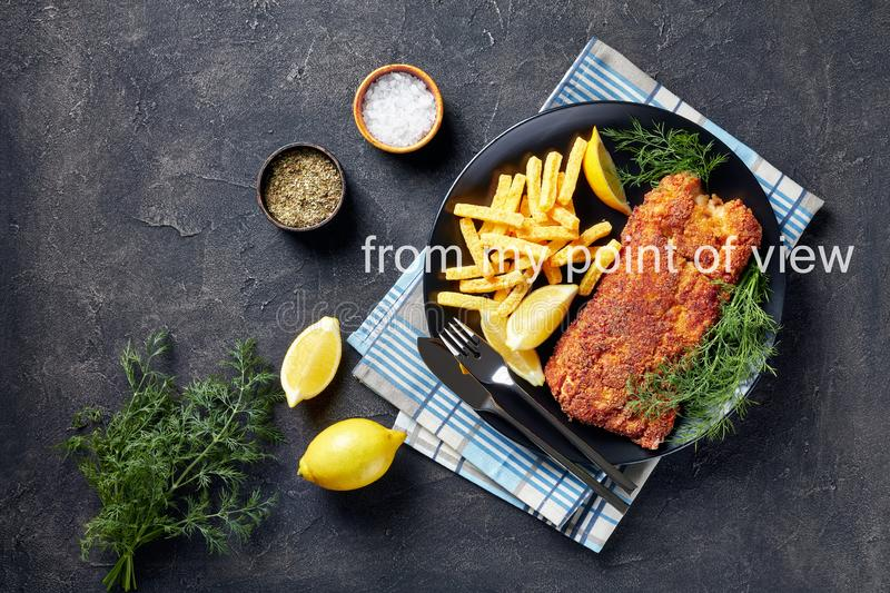 Close-up of Breaded hake fillet served with chips, fresh dill and lemon slices on a black plate on a white concrete table, stock images