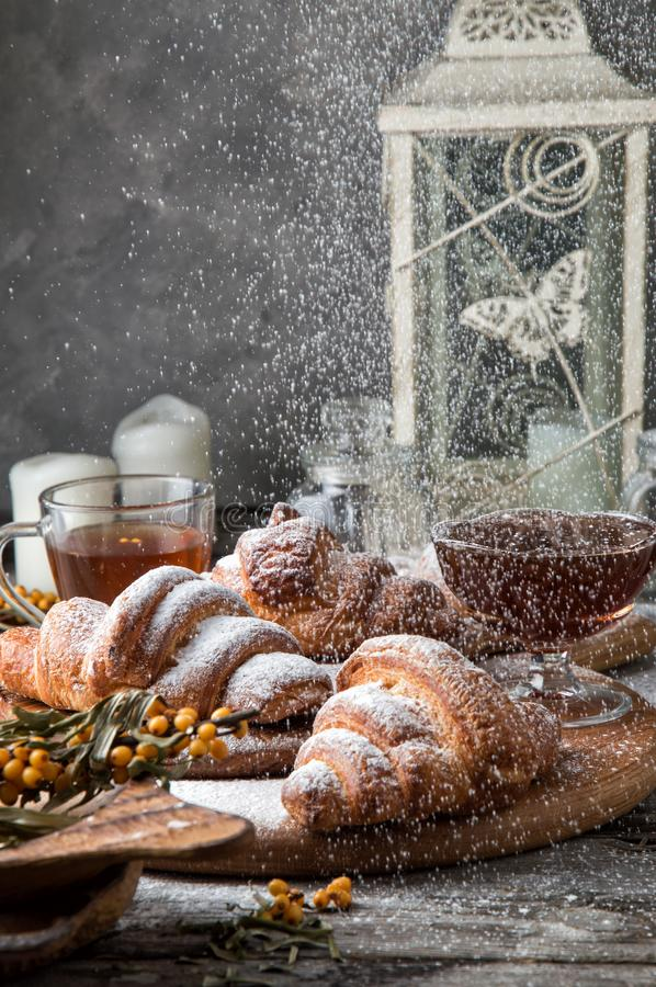 Close up. Breakfast with freshly baked french croissants, powdered on top white sugar powder. Winter fairytale morning royalty free stock photos