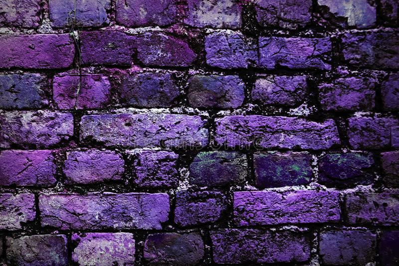 Close-up of brick wall with purple, pink color and black brick. Brick wall painted in bright colors. purplish bricks in the wall stock images