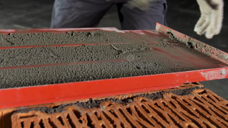 Close up of a bricklayer on a construction site with a trowel. Stock footage. Industrial worker using trowel for royalty free stock image