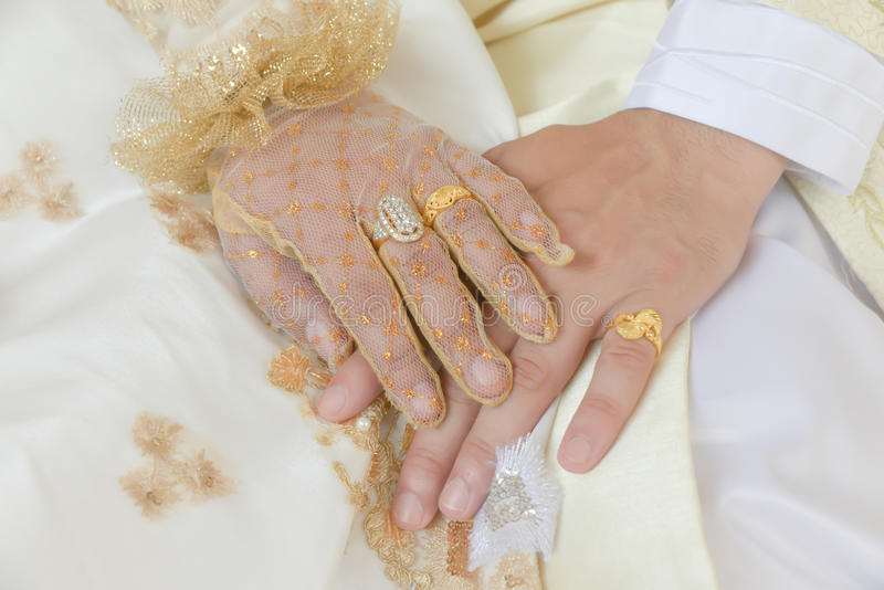 Close-up a bride and groom covers of each other's hands stock image
