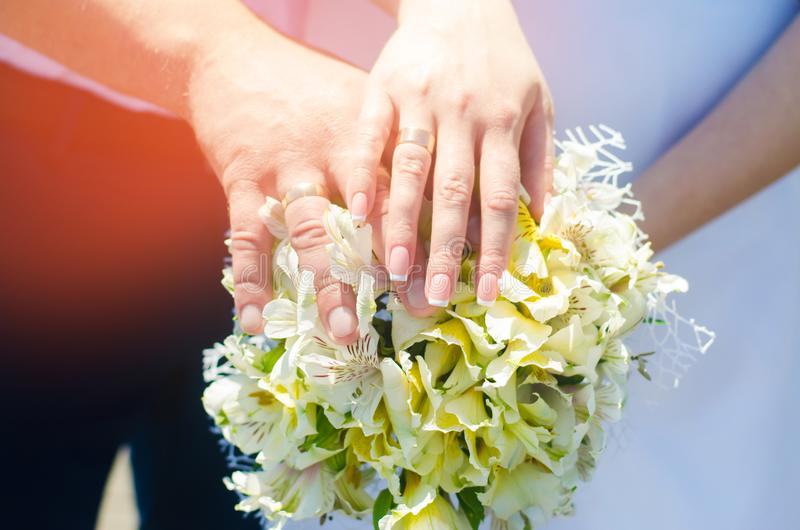 Close-up Bride and groom`s hands with wedding rings and bouquet. Love and marriage. Wedding accessories and decor on the backgrou stock photos