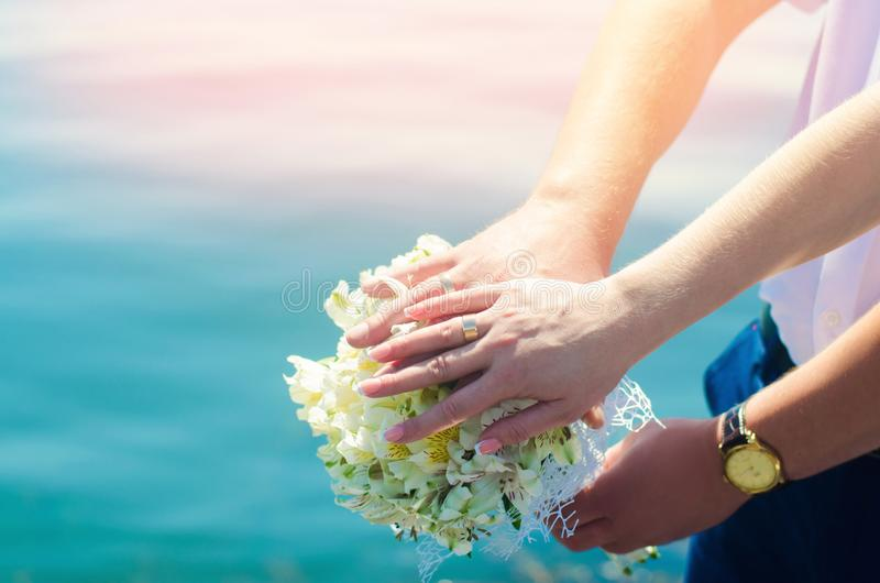Close-up Bride and groom`s hands with wedding rings and bouquet. royalty free stock photos