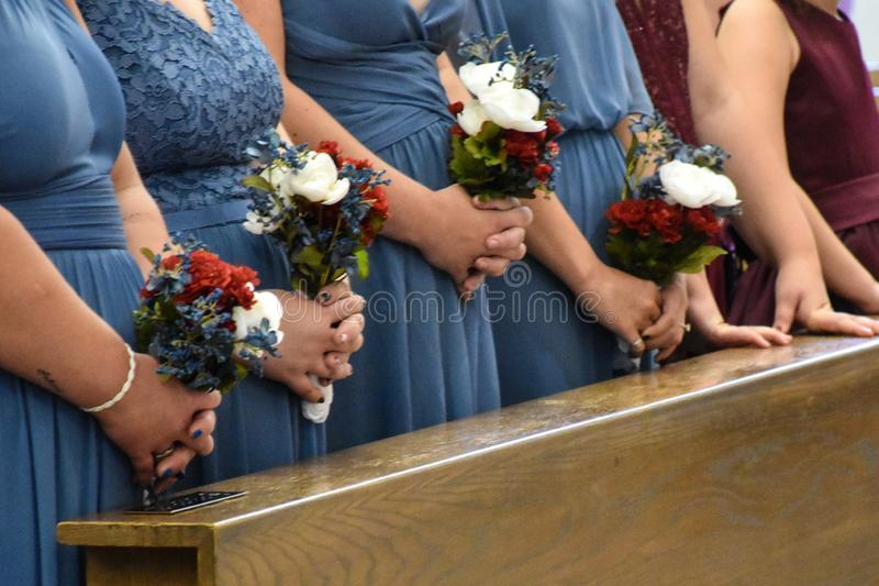 Close up of bridesmaids and flower girls torsos standing at wooden church pews formal church wedding ceremony. This is a close up of bridesmaids wearing blue stock image