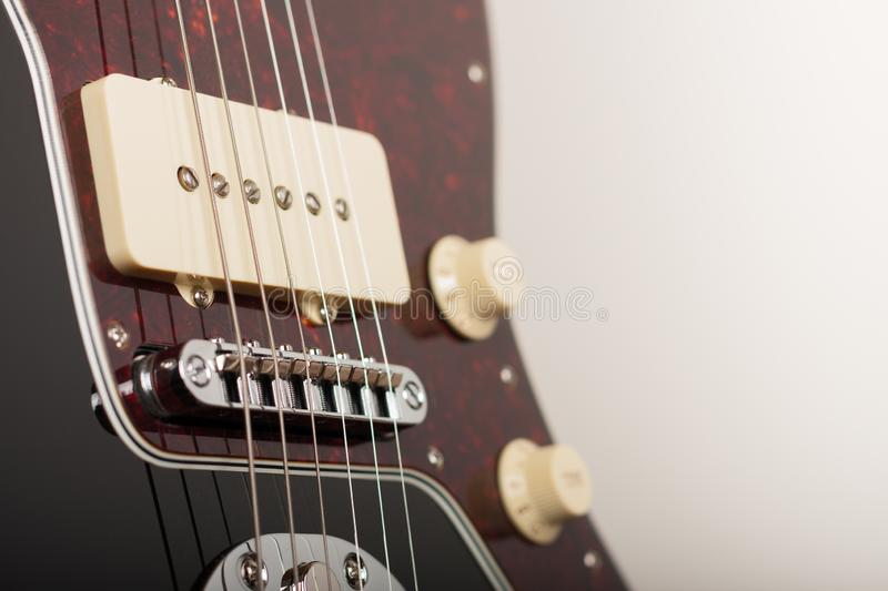 Close up of bridge and single coil on black  electric guitar, studio shoot. Close up of bridge and single coil on black electric guitar, studio shoot royalty free stock image