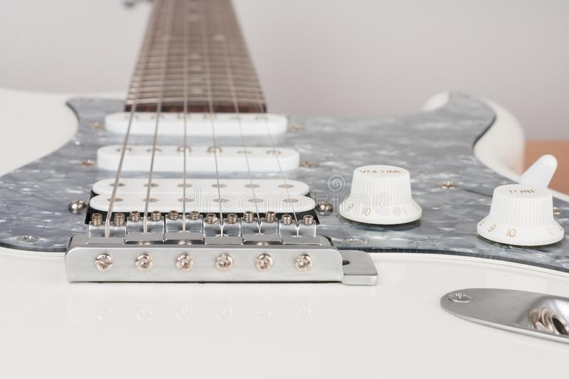 Close up of bridge of white electric guitar, studio shoot.  2 x Single Coil and 1 x Humbucking. Black Pearl pickguard.  stock images