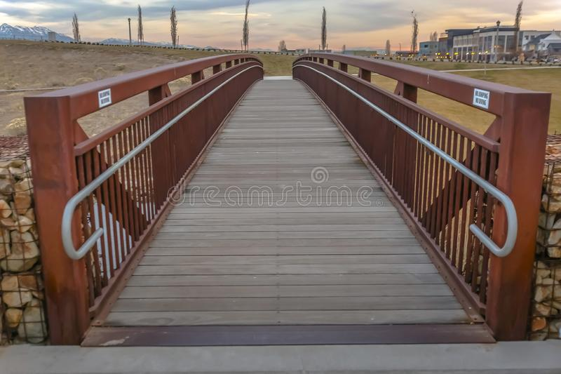 Close up of a bridge with a wooden deck and brown metal guardrails royalty free stock image