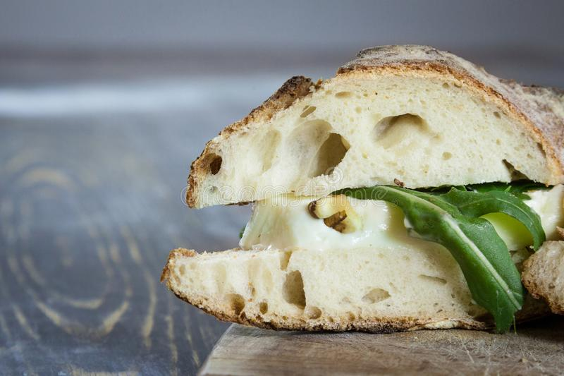 Close up Brie sanwdich in French baguette, made of Brie de Meaux Cheese with slices of rucola rocket salad and walnuts. This sandwich, in France, is called stock photos