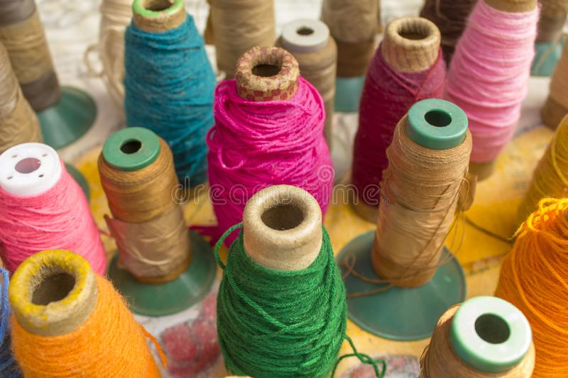 Close-up of bright multicolored spools of thread stand on the table surface against a blurred background. A close-up of bright multicolored spools of thread stock images