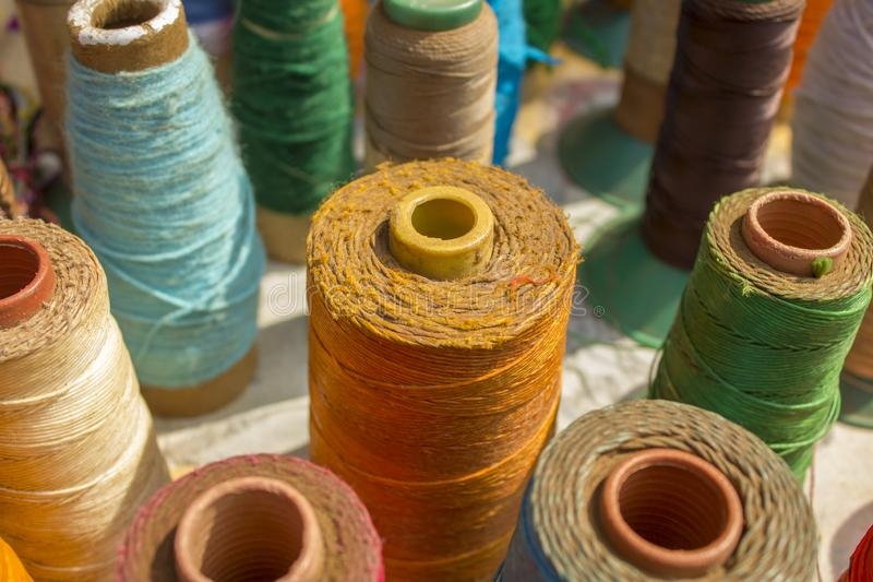 Close-up of bright multicolored spools of thread stand on a white tabletop against a blurred background stock image