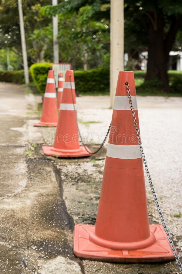 Close up bright orange traffic cones standing in a row on asphalt stock photography