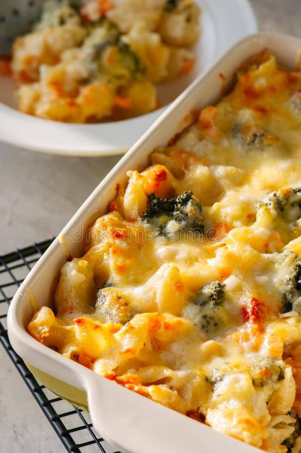 Close up of broccoli and pumpkin mac and cheese in a ceramic dis stock photography