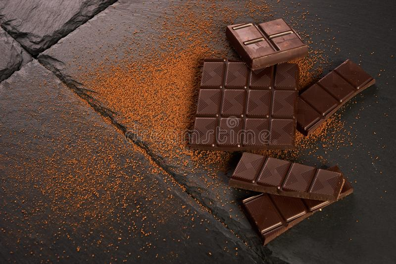 Close-up of broken chocolate pieces and cocoa powder. On dark stone background with copy space royalty free stock photo