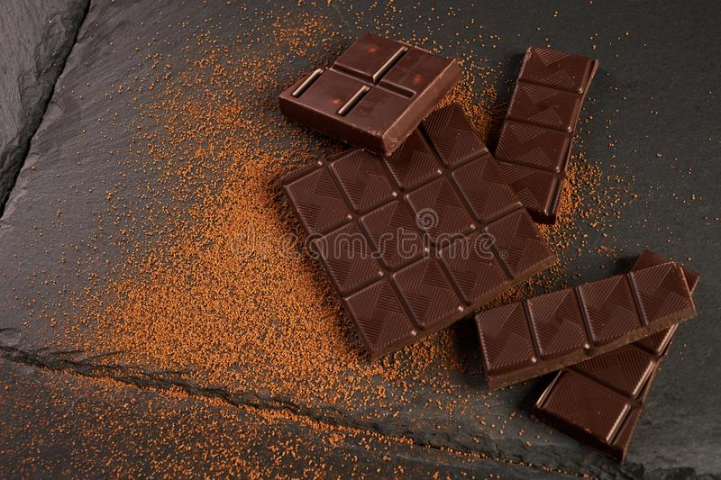 Close-up of broken chocolate pieces and cocoa powder. On dark stone background with copy space stock photo