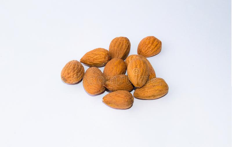 Close up of  brown almonds seeds isolated on white background royalty free stock photography