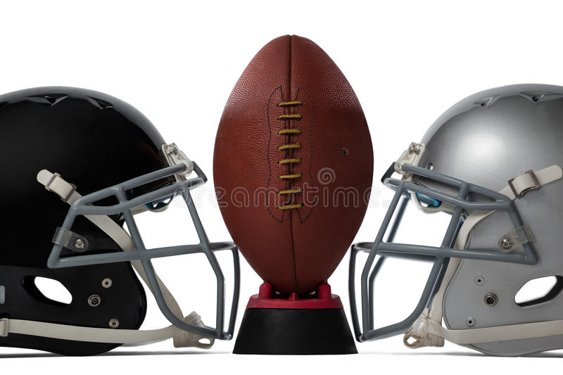 Close up of brown American football on tee by sports helmets. Against white baclground stock image