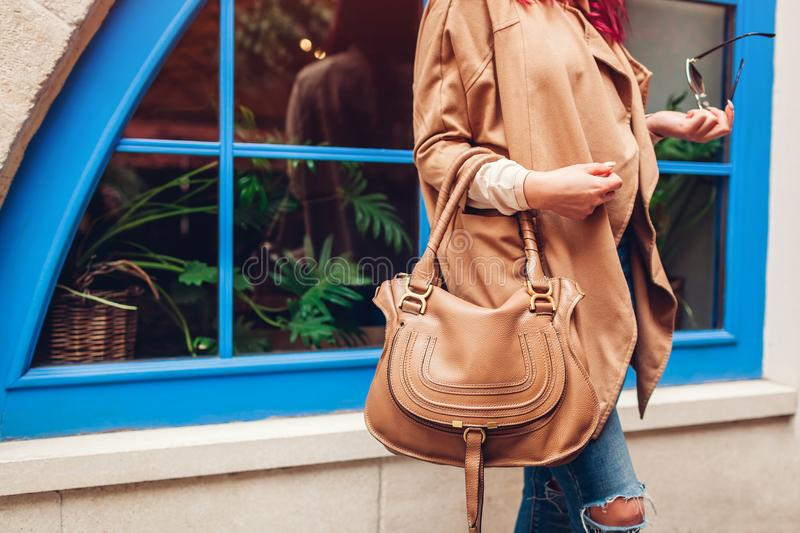 Close-up of brown female handbag. Woman holding leather bag and glasses outdoors. Fashionable accessories. And clothing stock photos