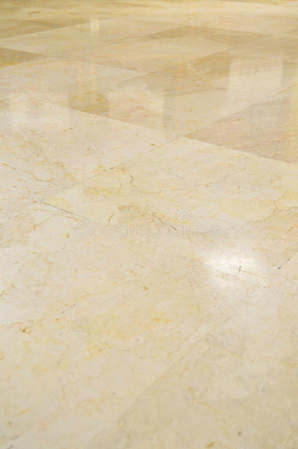Marble floor tiles. Close up of brown and gold marble floor tiles with reflection of lights royalty free stock photo