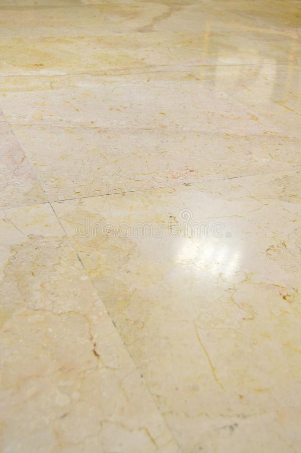 Marble floor tiles. Close up of brown and gold marble floor tiles with reflection of lights stock image